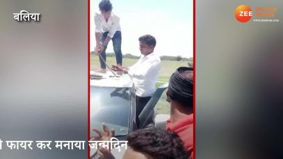 Ballia: Youth cuts birthday cake with sword on car roof, while friend fires gun in background